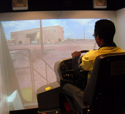 Photo of a heavy equipment driver training participant using a simulator